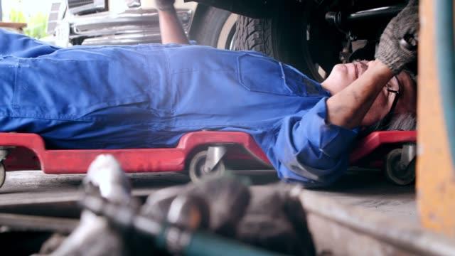 ワーク ショップ車のサービス、修理、保守および人々 のコンセプトで働いてショット、メカニックの年配の男性を台車します。 - 機械工点の映像素材/bロール
