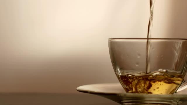 ドリーショット、お茶を注ぐ。お茶はガラス透明ティーカップに注がれています。ティータイム。透明なガラスのティーポットとティーカップ。 - マグカップ点の映像素材/bロール