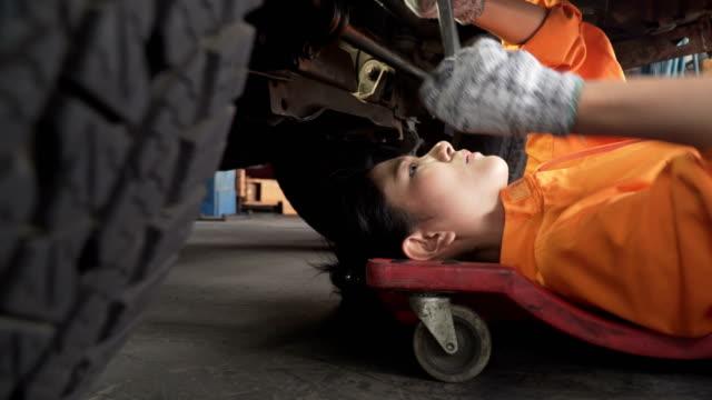 サイドビューをドリー: アジアの若い女性自動車整備自動車エンジンの下で働いて - 機械工点の映像素材/bロール