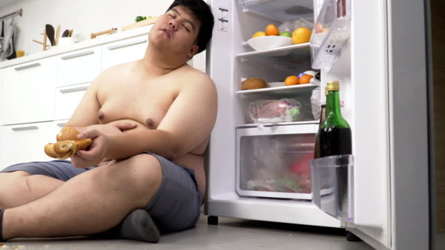 dolly side view: overweight Thai man eating until he sleeping at refrigerator dolly side view: overweight Thai man eating until he sleeping at refrigerator fat nutrient stock videos & royalty-free footage