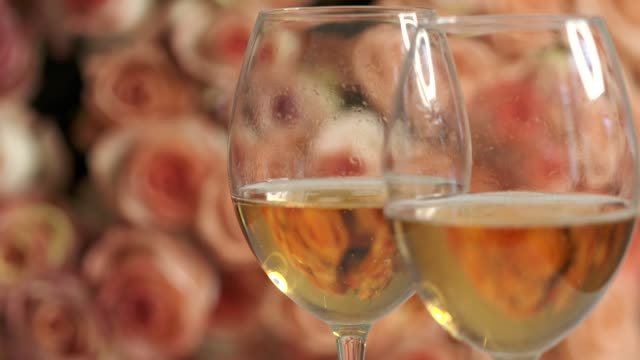 Dolly: Two glasses of sparkling wine and large bouquet of pink roses