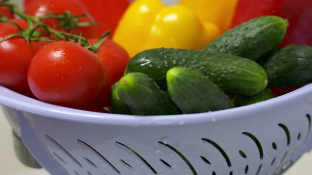 Dolly: Washed fresh vegetables with water drops in colander video