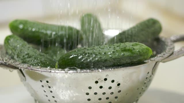 Dolly: Washing fresh cucumbers in steel colander under running water video