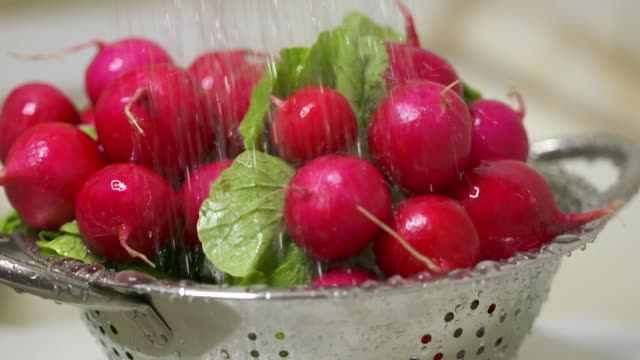 Dolly: Washing fresh radish with green leaves in colander under running water video