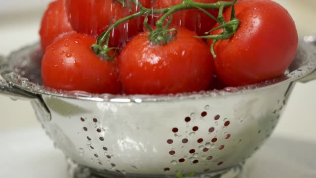 Dolly: Washing fresh tomatoes in colander under running water before eating video
