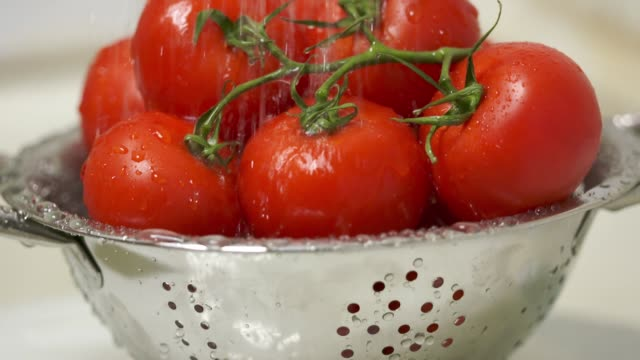 Dolly: Washing fresh tomatoes in colander under running water in slow motion video