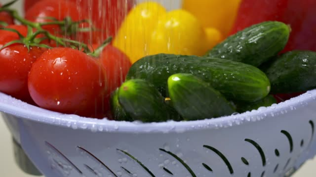 Dolly: Washing fresh vegetables in colander under running water in slow motion video