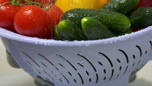 Dolly: Washing fresh vegetables in colander under running water video