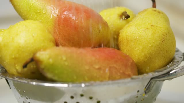 Dolly: Washing ripe yellow red pears in colander video