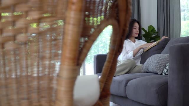 4k 돌리 와이드 샷 의 아름다운 젊은 아시아 여자 휴식 소파에 앉아 소파에 집 거실과 독서 소설 책. 예쁜 십대 소녀는 소파에 쉬고 주말에 혼자 집에서 읽는 것을 즐기고 있습니다. - 와이드 샷 스톡 비디오 및 b-롤 화면