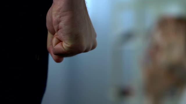 violenza domestica, uomo aggressivo farà del male a donna indifesa seduta sul pavimento - violenza donne video stock e b–roll