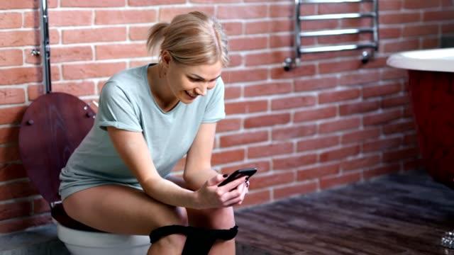 stockvideo's en b-roll-footage met binnenlandse jonge vrouw glimlachen met behulp van smartphone zittend op toilet at home badkamer - cell phone toilet