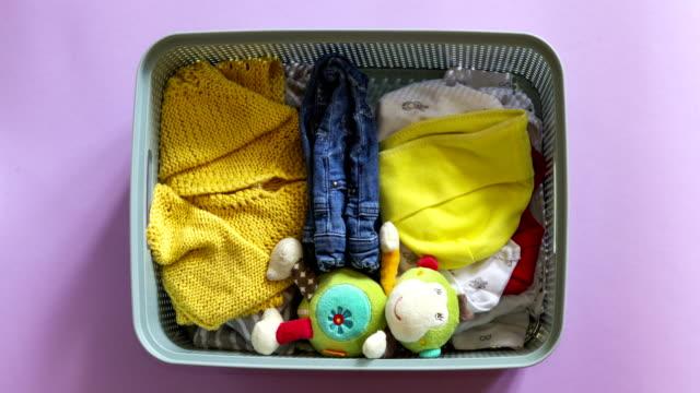 donation box with baby clothing stop motion animation. donate text. top view - abbigliamento da neonato video stock e b–roll