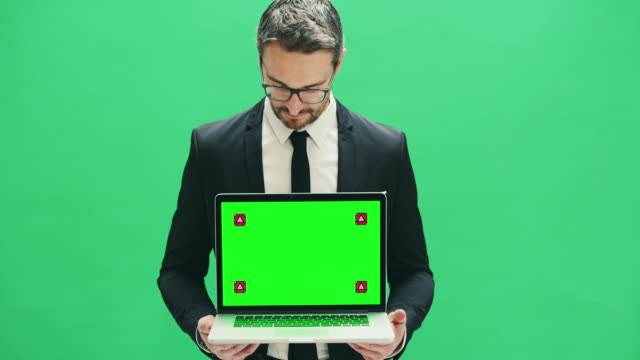Don't delay and display here 4k video footage of a businessman holding a laptop with a green screen display against a green background representing stock videos & royalty-free footage