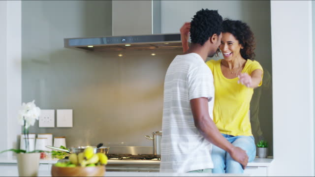Don't forget the food babe 4k video footage of a cheerful young man hugging his wife while she prepares food in the kitchen at home during the day falling in love stock videos & royalty-free footage