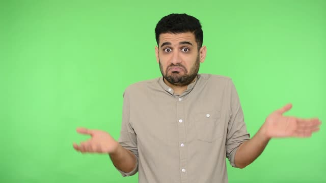 vidéos et rushes de je ne sais pas. homme de brunette confus haussant les épaules faisant le geste de questionnement., fond vert, clé de chrome - en désordre