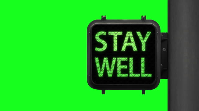 Don't Panic. Stay Well—Chroma Key shot of Green Walk Signal with hopeful phrase with green screen in the background