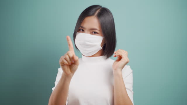 Don't Touch Your Face. Asian woman wearing hygiene mask showing hand stop sign and standing isolated over blue background. Health care concepts. 4k video. Don't Touch Your Face. Asian woman wearing hygiene mask showing hand stop sign and standing isolated over blue background. Health care concepts. 4k video. touching stock videos & royalty-free footage