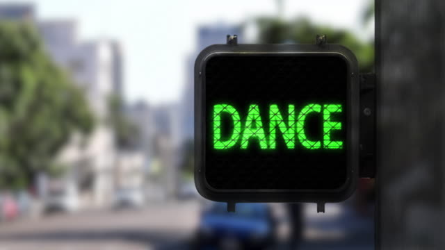 Don't Walk. Dance!—Medium shot of blinking Walk Signal with fun phrase