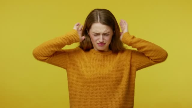 Don't want to listen. Upset girl in casual clothes covering ear with arms and saying no, not hearing talk Don't want to listen. Upset girl in casual clothes covering ear with arms and saying no, not hearing talk, ignoring loud noise, avoiding annoying sound. studio shot isolated on yellow background ear stock videos & royalty-free footage