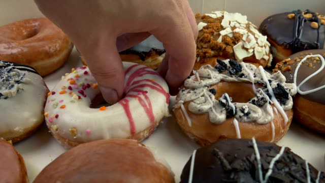 donut box opens and person takes one - bombolone video stock e b–roll