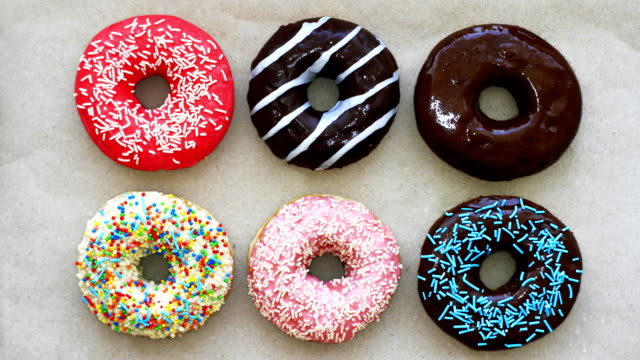 Donuts of different colors on cardboard, top view, stop motion animation. Full HD