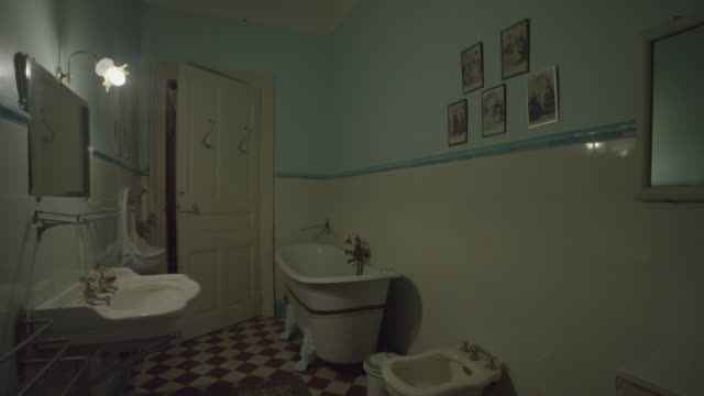 door of old haunted bathroom opening itself in abandoned house. ghost, spirit or demon. mirror on the side and old wash basin, bath, tub and bidet. red and white checkered floor. shot on red epic 6k. - ванная или туалет стоковые видео и кадры b-roll