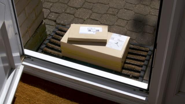 tür öffnet sich, um pakete auf der fußmatte zu offenbaren - schachtel stock-videos und b-roll-filmmaterial