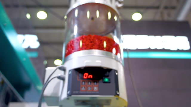 Dosing reservoir with red polymer pellets in extrusion equipment video