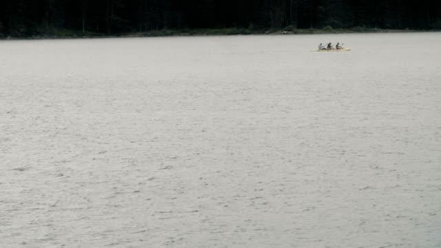 dospat/bulgaria-06.15.2018: three man kayaking in shiroka polyana dam at sunset in a moody day. - ekoturystyka filmów i materiałów b-roll