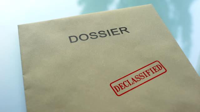 書類、機密解除された重要な書類をフォルダーにシールをプレス手 - クラシファイド広告点の映像素材/bロール