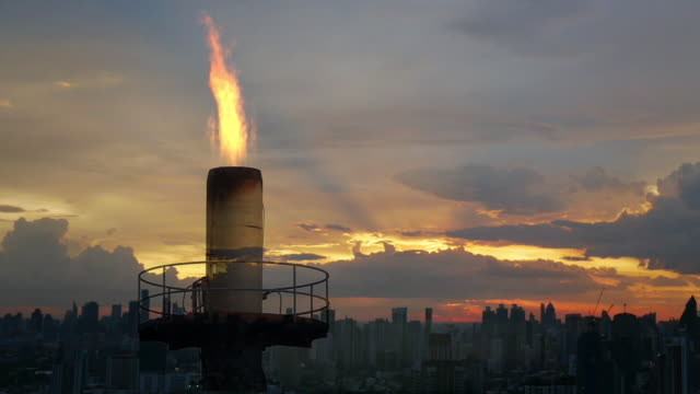 Double exposure fire flame from the combustion of oil refining with time lapse sunset over the city.