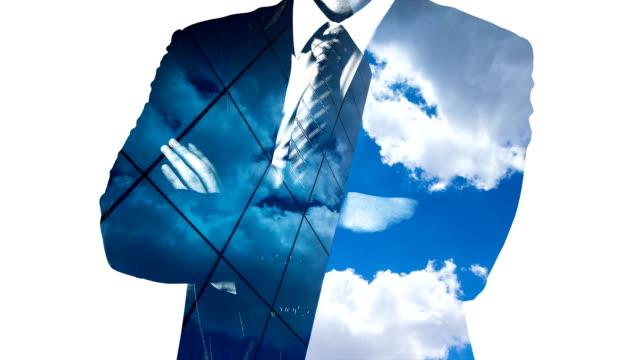 stockvideo's en b-roll-footage met dubbele blootstelling van zakenman en wolken tot uiting in de vele gespiegelde facetten van een moderne kantoorgebouw - dubbelopname businessman