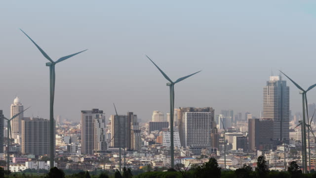 Double exposure wind energy turbines and downtown city. Prosperity and clean energy video