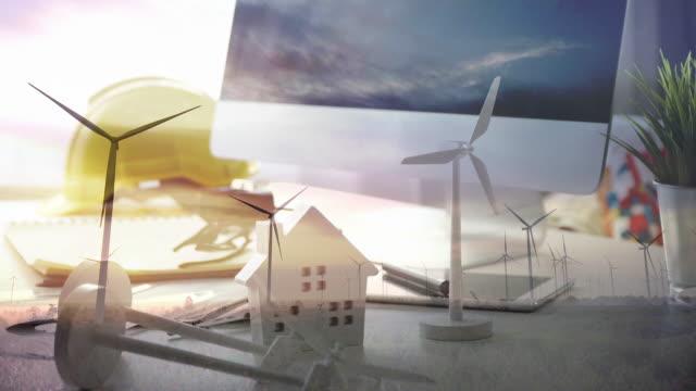Double exposure wind turbines models on engineers table with wind energy turbine. Mixed media on background