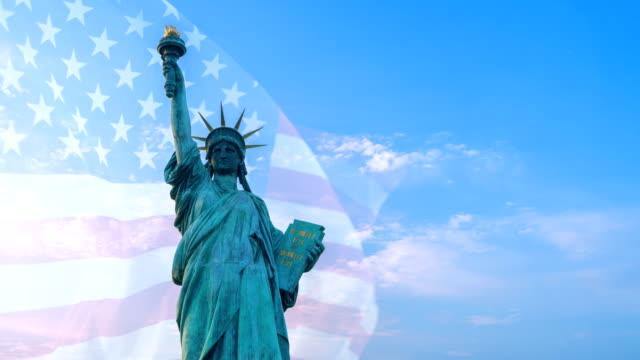 Doppelbelichtung mit Freiheitsstatue auf blauem Himmel und USA-Flagge weht im Wind mit Copyspace – Video