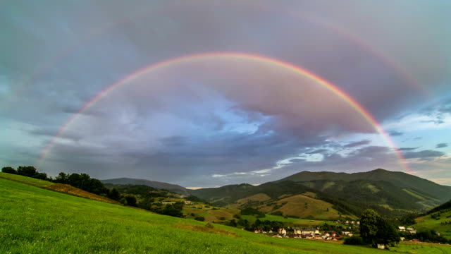 Double Rainbow over Green Meadow and Rural Landscape with Cloudy Sky Time Lapse video