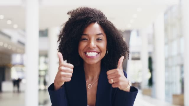 Double the effort, double the success 4k video footage of a happy young businesswoman giving thumbs up in a modern office thank you stock videos & royalty-free footage