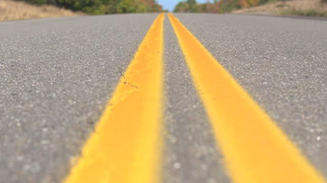 vídeos de stock e filmes b-roll de close up dof: double yellow lines road leading through colorful forest in autumn - alfalto
