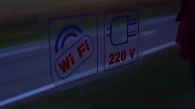 double-decker tourist bus. the bus has a 220 volt socket and wireless internet. sticker with a pointer 'free wi-fi' on the glass. car driving forward. Shooting on a sunset background. FullHD video