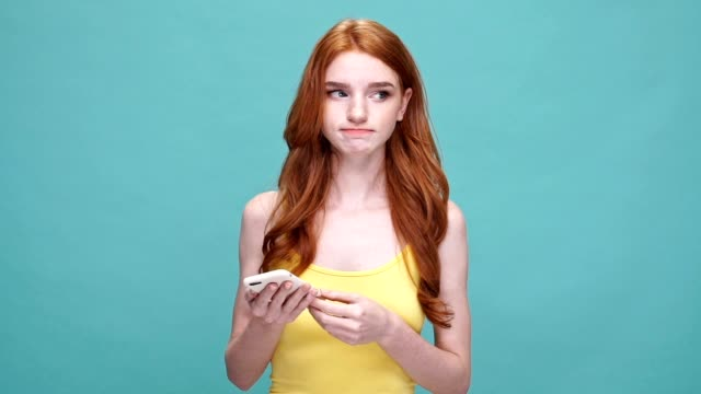 Doubtful pretty redheaded girl holding mobile phone while standing isolated over blue background video