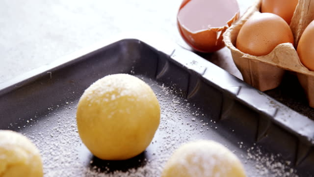 Dough balls with icing sugar on baking tray 4k video