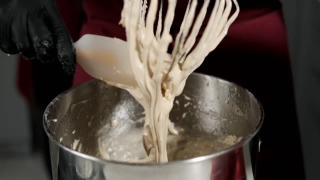 dough dripping from the whisk. woman prepares dough. hands in gloves - gluten free stock videos and b-roll footage