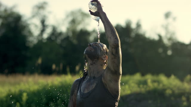Dousing Self With Water A female adult has completed a mud run. She is celebrating and cooling off by dousing herself with water from a water bottle. conquering adversity stock videos & royalty-free footage