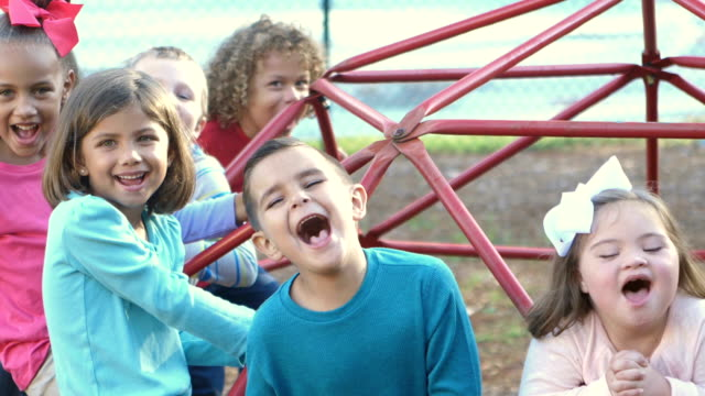 Down syndrome girl and friends on playground, shouting A group of seven multi-ethnic children, 5 to 7 years old, on the monkey bars on a playground, laughing and shouting. The girls with the white bow in her hair has down syndrome. disability stock videos & royalty-free footage