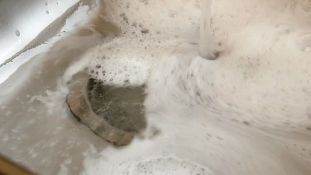 A down view of a kitchen sink filling up. Water with a detergent fills the kitchen sink. chlorine stock videos & royalty-free footage