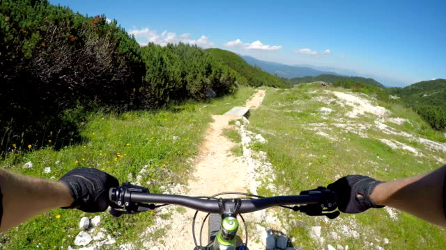 FPV: Downhill biker riding bike along the rocky trails and the wooden track video