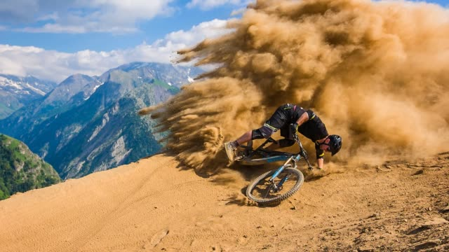 Downhill mountain biker falling on dirt road, leaving a cloud of dust behind