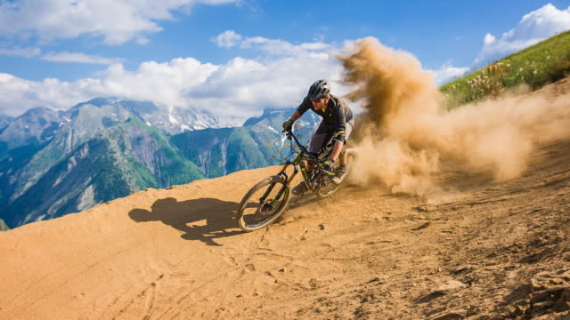 downhill mountain biker making a turn on dusty dirt road on a sunny day - hobby video stock e b–roll