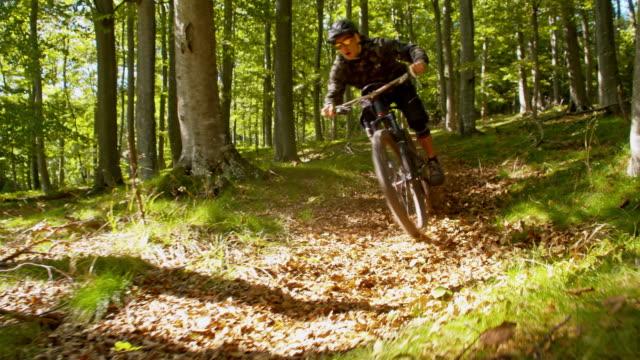 SLO MO Downhill mountain biker speeding through the forest video